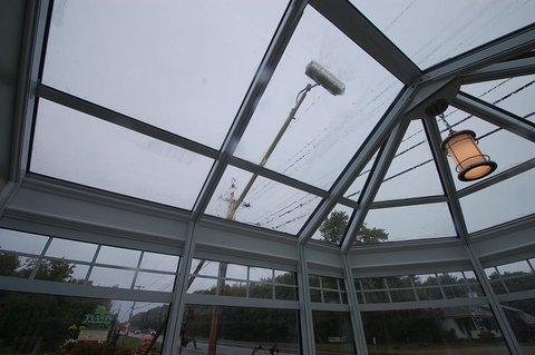 Solariums are easy to keep clean with a telescoping washer attached to a hose.  The glass of this sunroom is easy maintenance but as it is a display on the side of a busy road, it does get dirty.